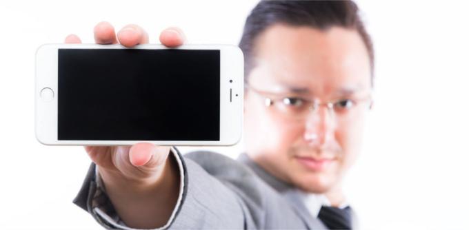 iPhoneを掲げる男性